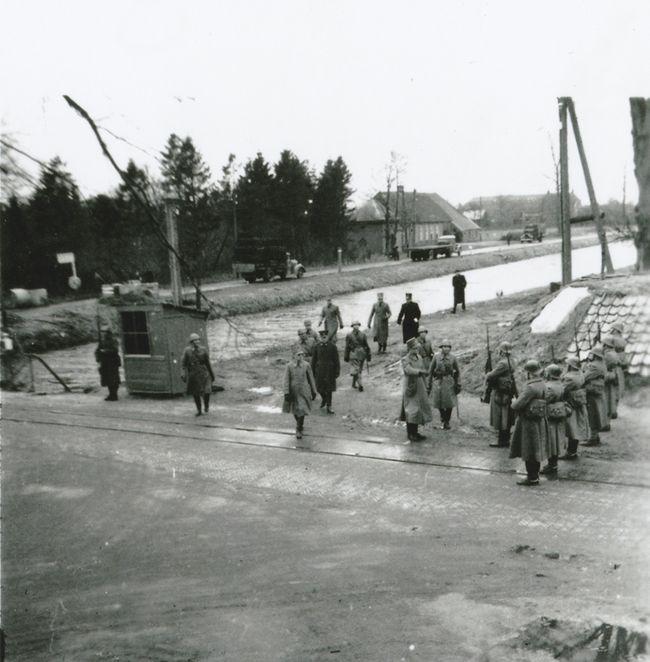 Aan de noordzijde van de brug exerceren de Nederlandse soldaten in 1940 naast het veldgeschut. Aan de overzijde van het kanaal de boerderij van de families Meijering en Keen. De tramrails zijn hier ook duidelijk zichtbaar