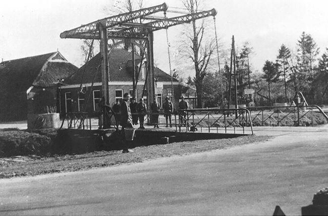 Café Welgelegen met Nederlandse soldaten op de brug en moeder Anninga op de voorgrond
